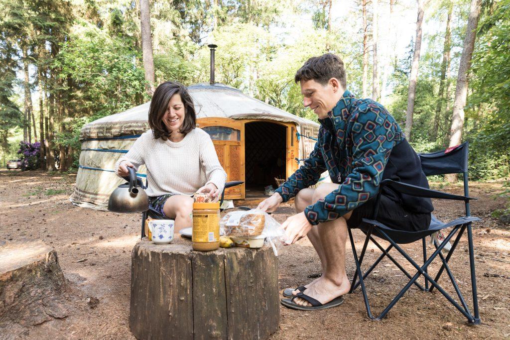 stel ontbijt op een boomstam voor hun tent op de camping